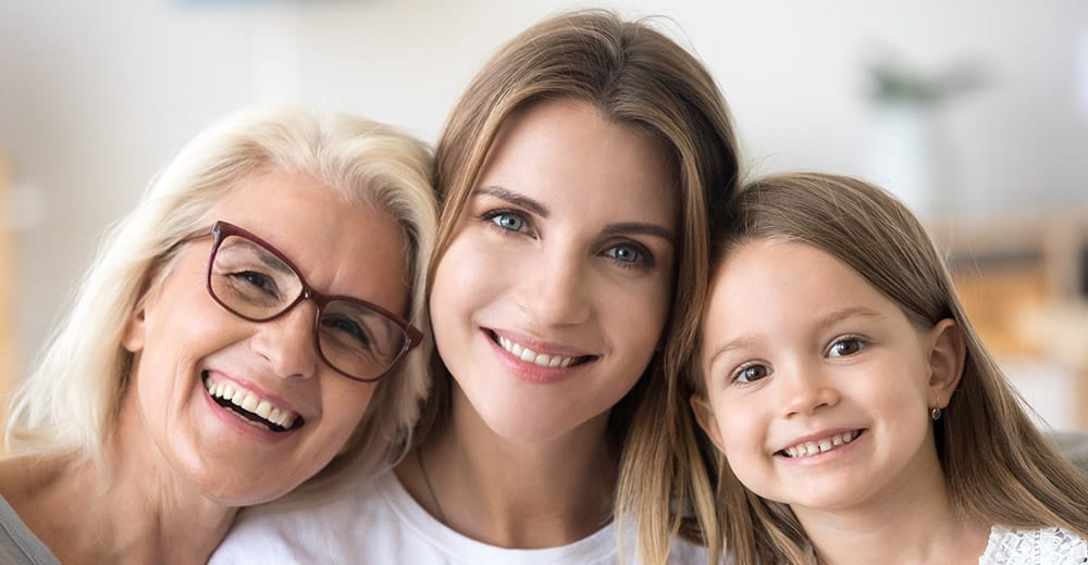 Three generations of dental patients smile happily.