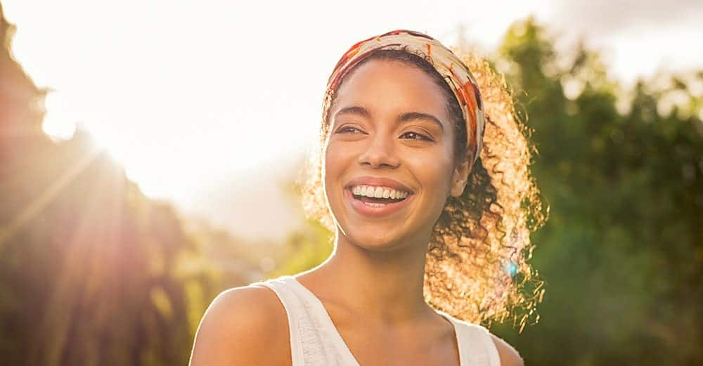 A woman with healthy, white teeth smiles broadly on a sunny day.